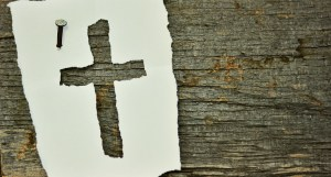 Paper cut out of a cross on wood