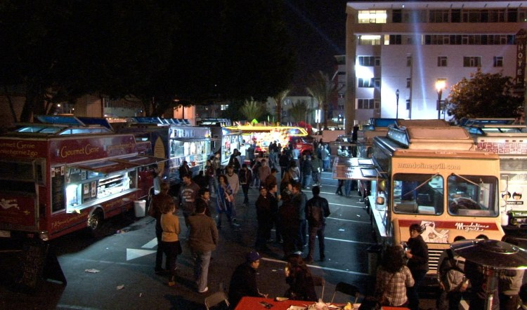 Huge crowd and rows of food trucks at evening event.