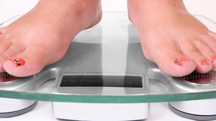 Female feet standing on a bathroom scale 000004093654 Small - Como perder os quilos extras de forma saudável