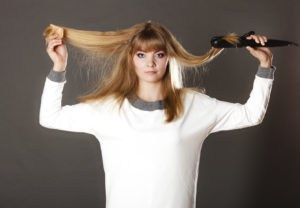 woman making hairstyle with hair iron 000074774197 Medium 300x208 - Como hidratar cabelos ressecados pelo frio