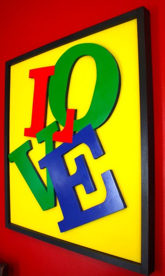 another tangled love affair : tangled letters on yellow background with black wood border