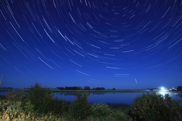 Star trails above a pond and field, near Minnedosa, MB.