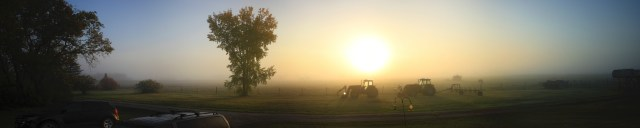 Panorama of a foggy morning at the farm, with a tree and two tractors halfway visible