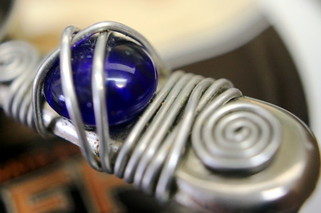 Blue cabochon on coffee scoop (macro)
