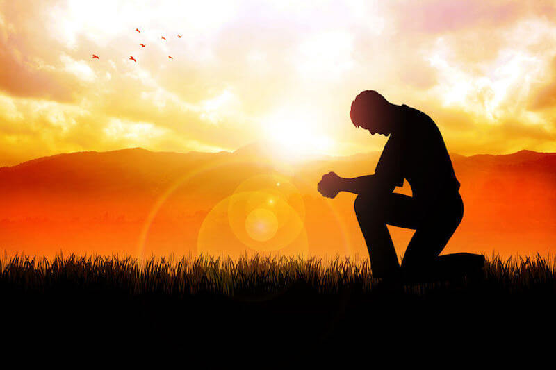Yielding to God in everyday life. A man praying, surrendered to God.