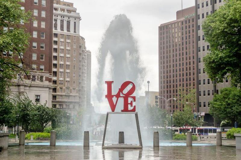 Brotherly love image showing a city square with the levers of love carved on a stature
