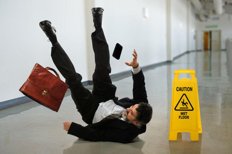 Fallen from grace image showing a businessman falling by a fall sign on a wet flour