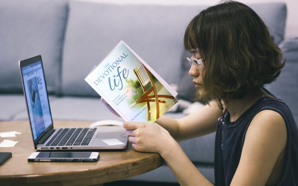 The devotional life book in a woman's hands in front of a computer