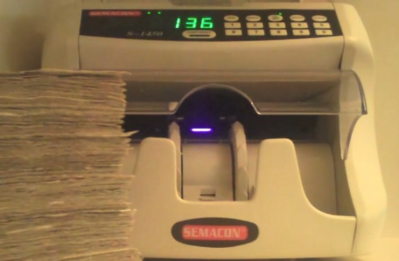 This Semacon cash-counting machine appears as a stage prop in a cash-gifting video advertised in Home Business Advertiser.