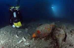 Un arqueólogo, junto a las ánforas que transportaba el barco romano que se ha localizado en las proximidades de las islas Formigues. El Periódico
