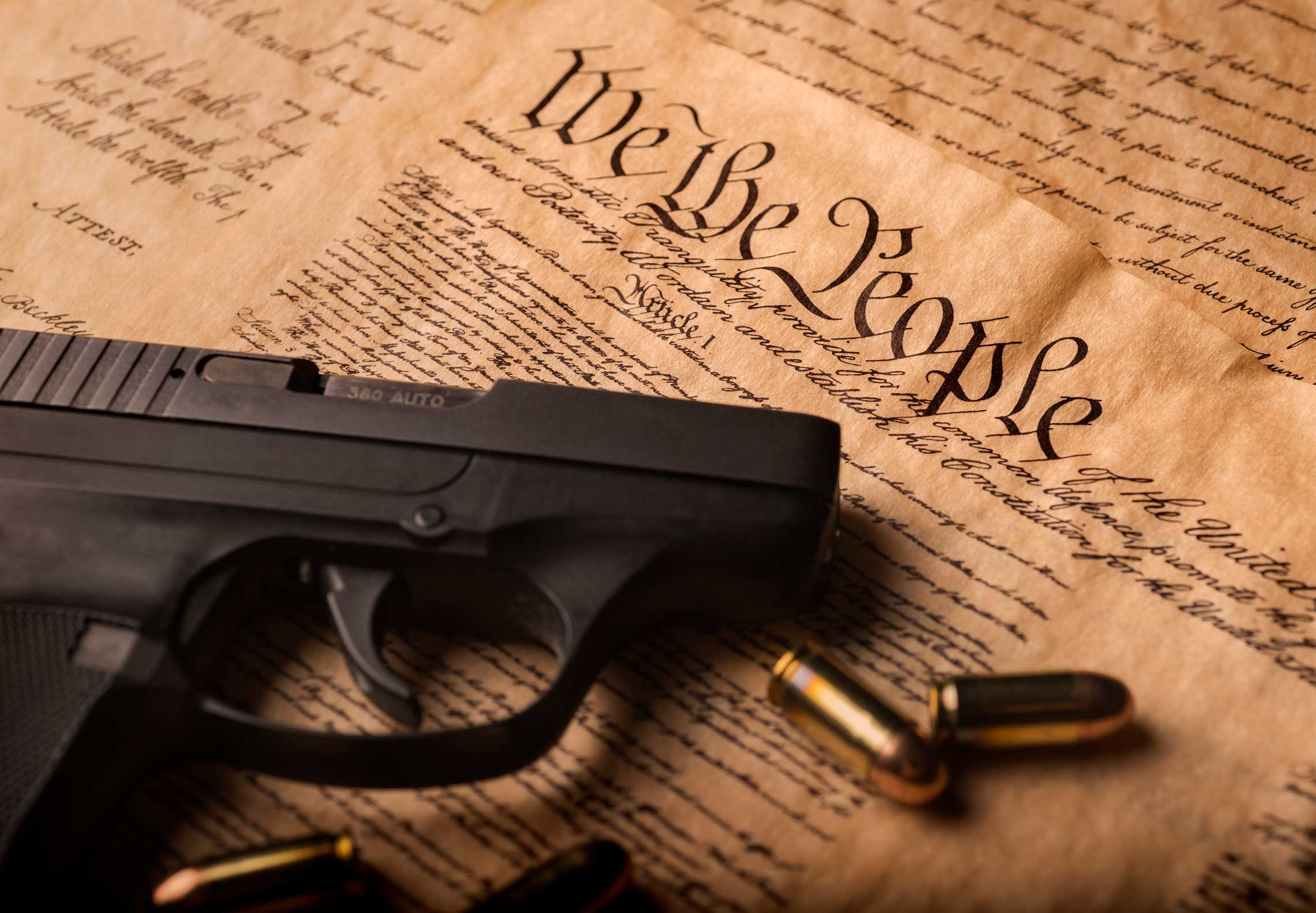 A handgun sitting on top of the United States Constitution