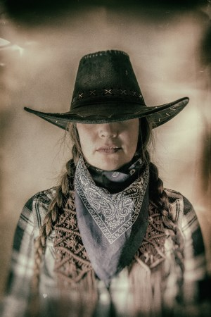 Old West Cowgirl Hat Low Wide. Old west cowgirl with hat low blocking eyes, edited in vintage film style.