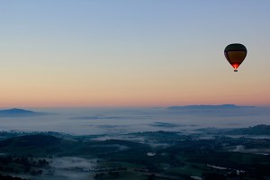 A hot air balloon at sunset flying over low mountains