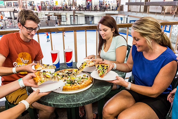 Diners digging in to a pizza while overlooking the indoor ice skating rink.
