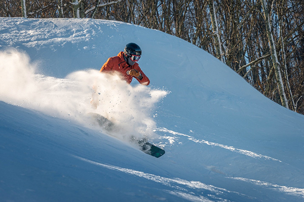 A snowboarder spraying snow while making their way down the mountain.