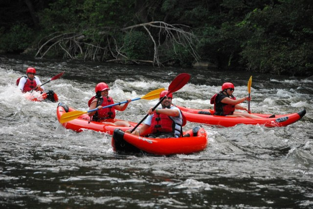A group of kayakers on a river in the Smoky Mountains