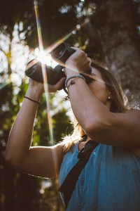 A woman with binoculars in the forest