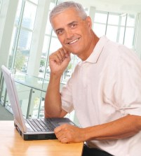 Man-with-laptop-on-desk-smiling-at-camera-in-office-