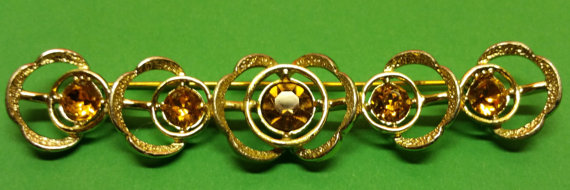 Sarah Coventry bar style pin with gold tone amber-jet rhinestones. Vintage and gorgeous!