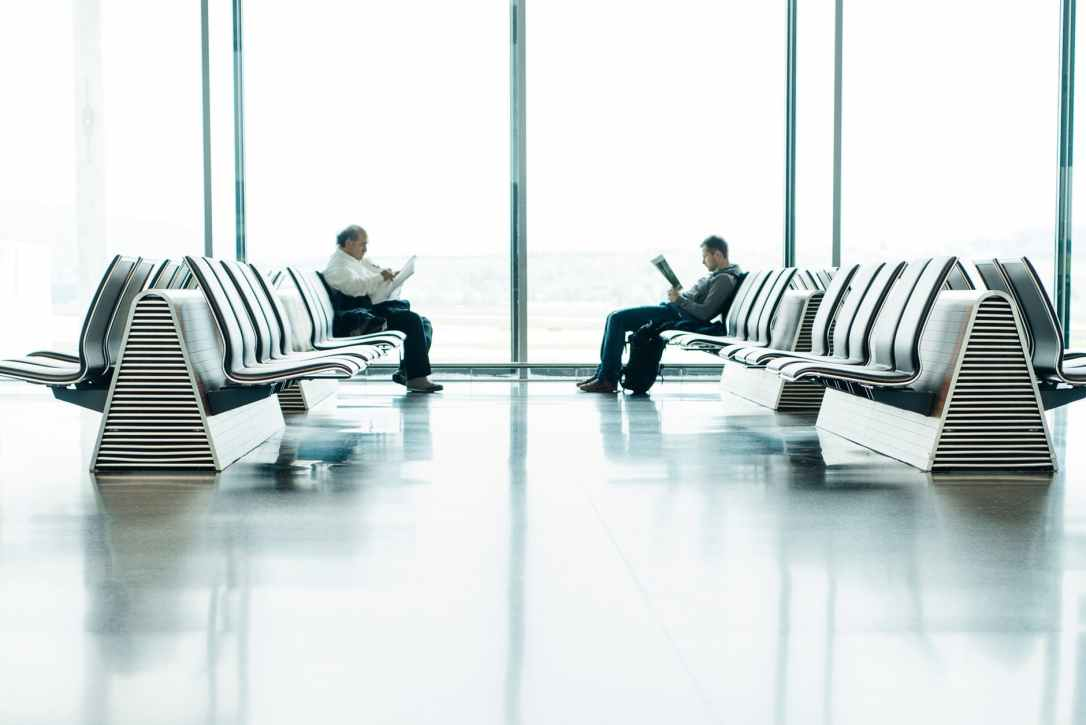 two men sitting in front of each other on white gang chairs in airport waiting area