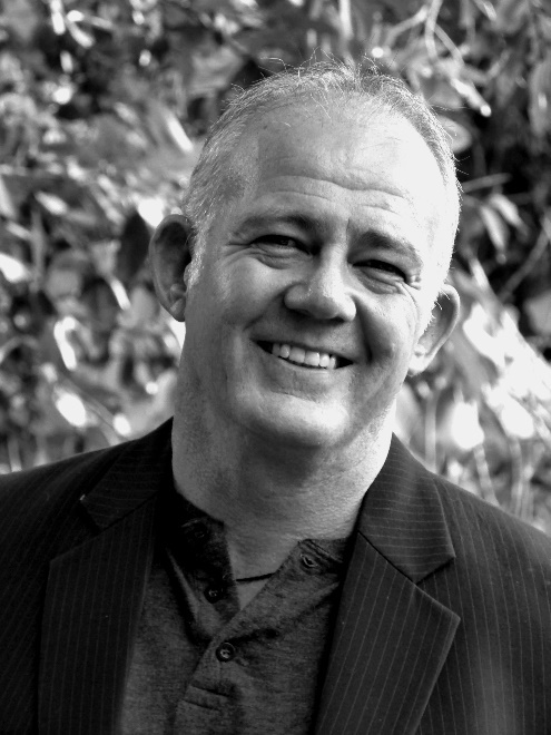 A black and white photo of Rob Shackleford, standing outside with a background of leaves. The foreground is a smiling Rob with his head slightly leaning to the right. He is wearing a dark button up shirt and a black blazer jacket.