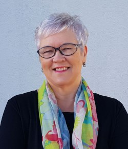 A photo of Sally Cronin, a smiling woman with short silver hair and almond shaped glasses, standing in front of a light gray background. She wears a black shirt and has a colorful gauzy scarf draped around her neck.