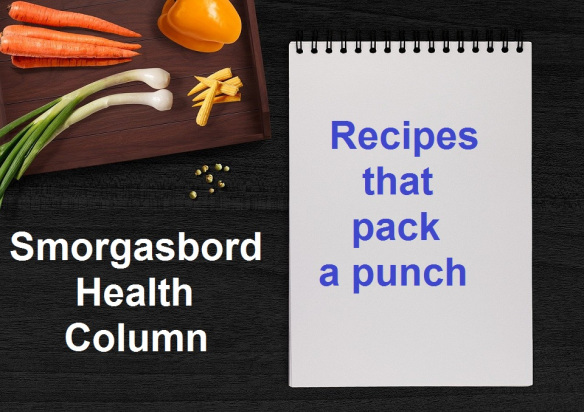 """A wooden cutting board and a spiral-bound notepad are on a dark table, as seen from above. The board has baby corn, green onions, a yellow pepper, and orange carrots, waiting to be chopped. A sprinkling of beige coriander seeds sit beside the board. White text is visible over the table and reads """"Smorgasbord Health Column"""" while blue text over the notepad reads """"Recipes that pack a punch""""."""