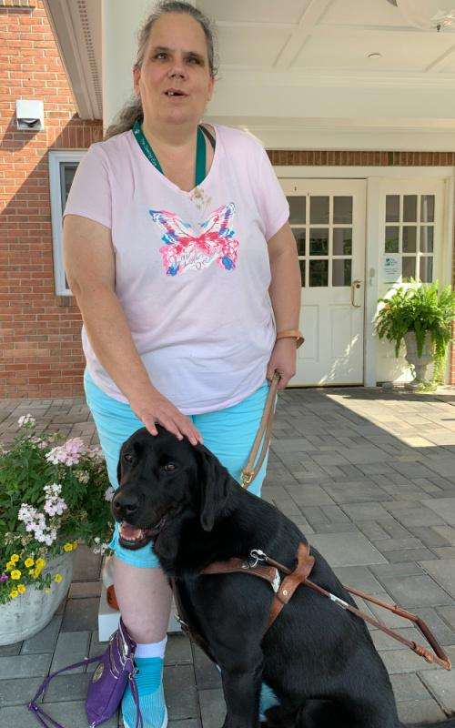 Patty and her guide dog Blue. Patty has her hair tied back in a low ponytail and rests her right hand on Blue's head. She wears a white shirt with a pink and purple butterfly on the front and light blue shorts. Blue is a handsome black lab. He wears a brown leather harness with a handle attached to the back and is smiling at the camera as he sits in front of Patty. In the background is a brick building with white, windowed doors and a flowerpot overflowing with pink and yellow blooms.