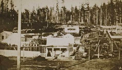First photograph of Seattle shows Henry and Sarah Yesler's home in Pioneer Square ca. 1859. Sarah poses on their front porch.  Photo by E. A. Clark