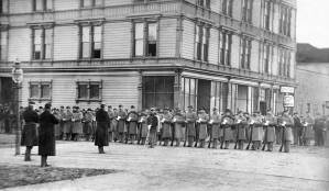 Then: The Pacific House, behind the line-up of white-gloved soldiers, might have survived well into the 20th Century were it not destroyed during Seattle's Great Fire of 1889. Courtesy, Museum of History and Industry
