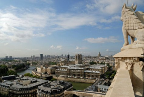 """Notre Dame, the Pantheon and the relatively modest skyscraper horizon of Paris """"suburbs"""" to the southeast from Tour St. Jacques. The statue of the bull on the right represents one of the four evangelists."""