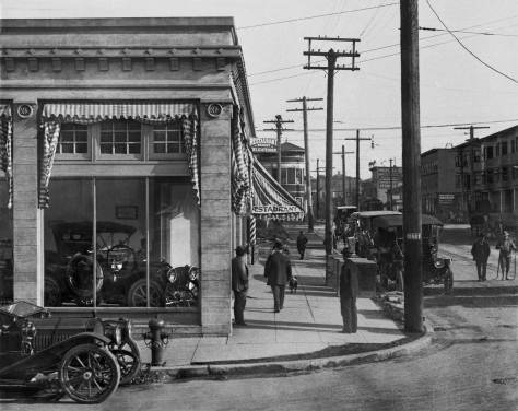 THEN: The brand new N&K Packard dealership at Belmont and Pike in 1909.  Thanks to both antique car expert Fred Cruger for identifying as Packards the cars on show here, and to collector Ron Edge for finding them listed at this corner in a 1909 Post-Intelligencer. (Courtesy Museum of History and Industry.)