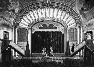"THEN: Seattle Architect Paul Henderson Ryan designed the Liberty Theatre around the first of many subsequent Wurlitzer organs used for accompanying silent films in theatres ""across the land"". The Spanish-clad actor-dancers posed on the stage apron are most likely involved in a promotion for a film – perhaps Don Q, Son of Zorro (1925) or Douglas Fairbanks' The Gaucho (1929) that also played at the Liberty. (Courtesy Lawton Gowey)"