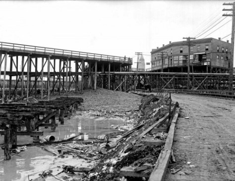 Another 1908 look into the neighborhood being raised during the Jackson Street Regrade.  The top of the Great Northern tower pokes between the elevated building on the right and the trestle on the left.  Courtesy, Museum of History and Industry aka MOHAI.