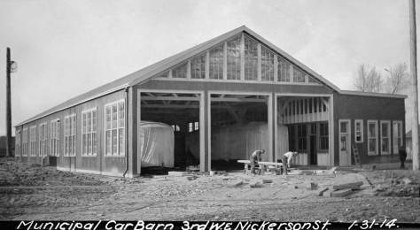 The Seattle Municipal Railway's first dedicated car barn was built in 1914 on Third Ave. W. about mid-way between the campus of Seattle Pacific College and the construction then underway of the Lake Washington Ship Canal.  (Courtesy Lawton Gowey)