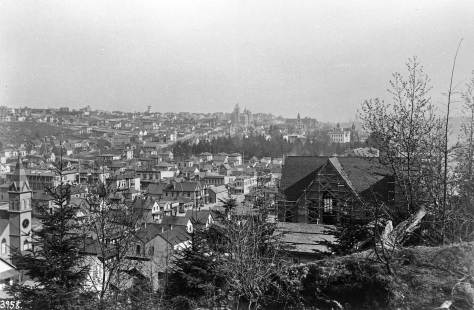 With the steeple of the new Norwegian Danish Lutheran sanctuary on the left, and construction still on the Methodist Protestant Church, on the right, this F. Jay Haynes photo looks southeast from Denny Hill to First Hill.  Note the greenbelt of the university campus at the scene's center.  The green reaches north as far as Union Street, the border there of the original campus.