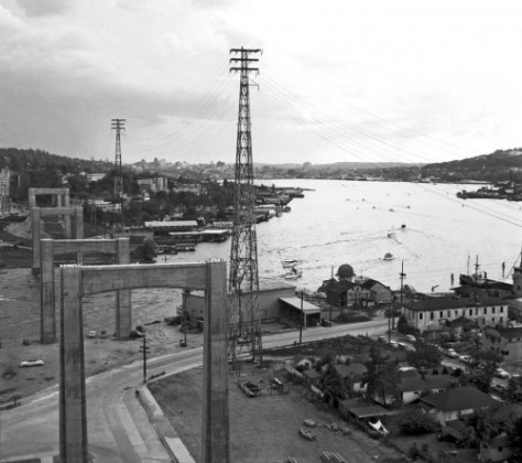 This for some agoraphobic look north through the construction line for the Lake Washington Ship Canal Bridge includes a late glimpse of the Latona Hotel, far-right, across Northlake from it the Wigwam Shingle Mill.  This rare capture is shown again in one of the three linked photos featured below.