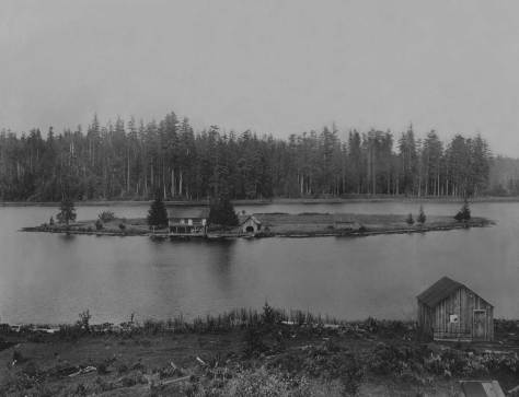 "THEN: Julia and Richard Ballinger owned a ""gas-powered"" rowboat to reach their summer home on their namesake Lake Ballinger.  This 1911 view looks east from near the tracks of the Seattle-Everett Interurban.  (Courtesy, Ron Edge)"