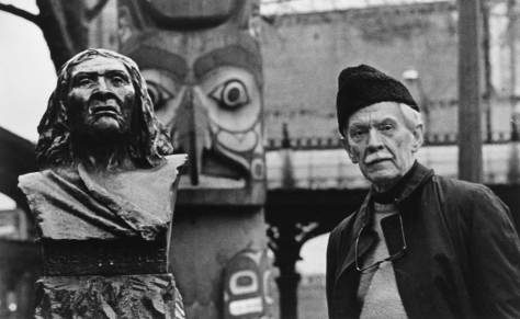 Celebrated photographer Mary Randlett's portrait of historian Murray Morgan (author of Skid Road and other classics) posing with two other Pioneer Place (or Square) totems.