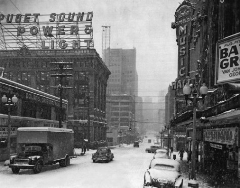 A few blocks east on Olive below the Music Hall's marque showing M.G.M.s Van Johnson vehicle, Battle Ground during its winter run here in 1950.  Puget Sound Power's headquarters at the southwest corner of Olive and 7th have corporate continuity with the Seattle Electric facilities shown above.