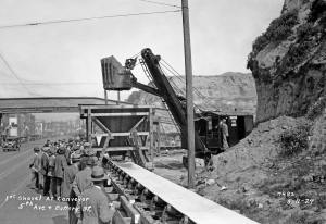 """THEN: Before this the first shovel of the last of Denny Hill was ceremonially dropped to the conveyor belt at Battery Street, an """"initial bite of 30,000 cubic yards of material"""" was carved from the cliff along the east side of 5th Avenue to make room for both the steam shovel and several moveable belts that extended like fingers across the hill. It was here that they met the elevated and fixed last leg of the conveyor system that ran west on Battery Street to the waterfront. (Courtesy, Seattle Municipal Archive)"""