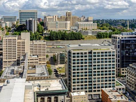 "NOW: Center-right, the King County's ""green"" Chinook Building stacks thirteen stories above the northwest corner of 5th and Terrace.  Behind it and up Jefferson Street at its southwest corner with 6th Avenue is the county's also new Goat Hill Parking Garage."