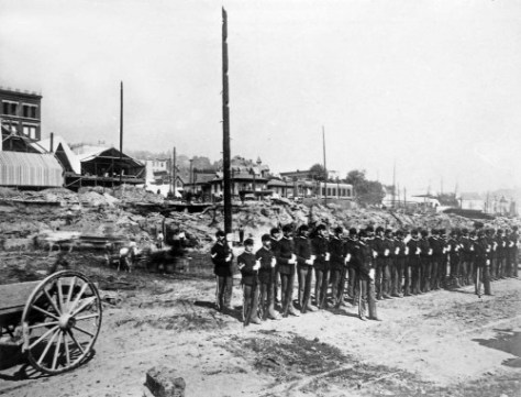 The Seattle Rifles, protecting the ruin property, stand on guard at the northeast corner of Columbia St. and Front or First Avenue.  Had it survived the first, the rear of the station would appear on the far left.  Note near the subject's center the tower of the Yesler Mansion on 3rd at Jefferson.
