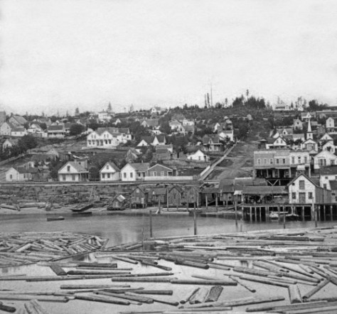 One half of a Peterson & Bros stereo card of the waterfront at the foot of Columbia Street recorded from the dogleg end of Yesler's Wharf.   The Elephant Store, at the southeast corner of Columbia and Front (First) stand in front of the future site of the first fire station.  Curiously, even here in 18978 there is a tower showing its head behind the store.  Curious.  The clump of trees on the horizon is near 7th/8th Avenue.  Soon we may have this estimate refined as we (Rod Edge, Greg Lange and I) are now studying the deforestation of First Hill, but not quite yet.