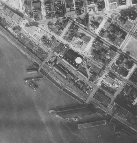 The 1929 aerial with the Union Oil facilities and its Bay Street dock, left of center, and below it the Pier 70 dock (still name Pier 14 then) below it.  Denny Way runs across the top of the subject. The seawall here is still seven years from completion.  (Courtesy Seattle Municipal Archive)