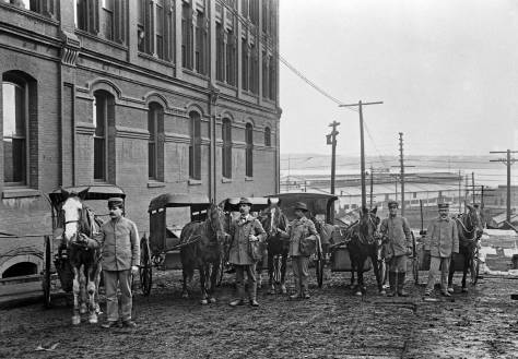 THEN: Looking west from First Avenue down the University Street viaduct to the waterfront, ca. 1905. Post Office teams and their drivers pose beside the Arlington Hotel, which was then also headquarters for mail delivery in Seattle. (Courtesy, Gary Gaffner)