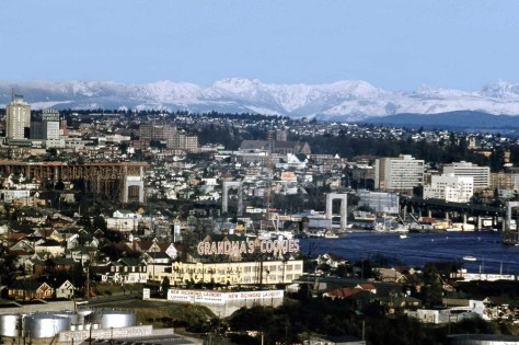 A detail of Lawton Gowey's Jan. 17, 1960 look east from Queen Anne Hill over Grandmas Cookies in Wallingford and further to construction on the Lake Washington Ship Canal Bridge, the University and its district, and the Cascades on a clear winter day.  (By Lawton Gowey)