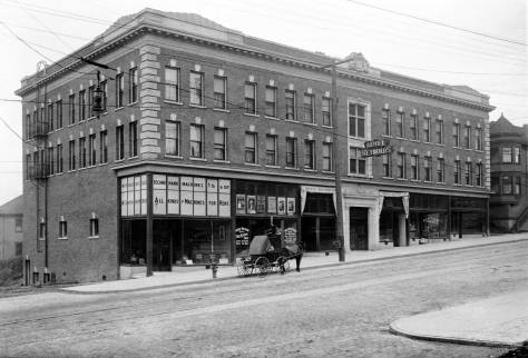 THEN: Beginning with the Reynolds, three hotels have taken tenancy in this ornate three-story brick block at the northeast corner of Boren Avenue and Pike Street. (Courtesy Lawton Gowey)