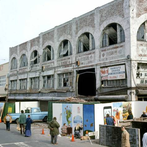 "THEN: In this April morning record of the 1975 ""Rain or Shine Public Market Paint-in,"" above the artists, restoration work has begun with the gutting of the Corner Market Building. (Photo by Frank Shaw)"