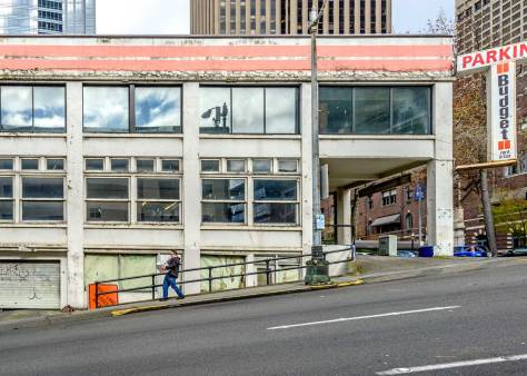 """NOW: The parking garage, at what was the Hunt's corner, was built in 1923 and survives as an unheated shelter for a few dozen cars.  This Central Business District corner is valued by the taxman at more than four-and-one-half thousand times the value of this reinforced concrete """"improvement.""""  The Rainier Club, its neighbor across Four Avenue, can be glimpsed on the right."""